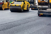 Road roller leveling fresh asphalt pavement — Stock Photo
