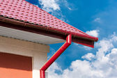 Gutter and red tiled roof — Stock Photo