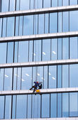 Window cleaner working on a glass facade — Stock Photo