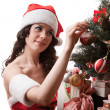 Santa girl decorates Christmas tree. — Stock Photo #15794009
