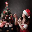 Santa girl decorates Christmas tree. — Foto de Stock