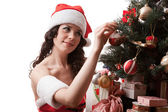 Santa girl decorates Christmas tree. — Stock Photo