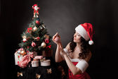 Santa girl decorates Christmas tree. — Stock fotografie