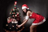サンタガール オープン引くクリスマス ツリー. — ストック写真