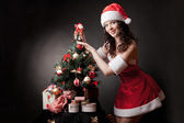 Santa girl decorates Christmas tree. — Stockfoto