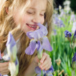 Little girl smelling flower — Stock Photo #1249965