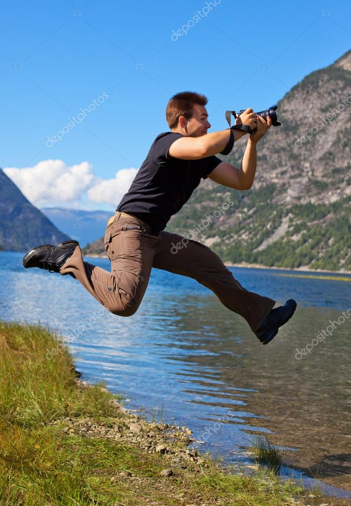 Young photographer shooting nature in the jump. — Stock Photo #12557656