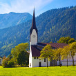 Alps village with cathedral — Stock Photo