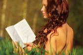 Young naked woman reading book — Stock Photo