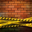 Caution ribbon on brick wall — Image vectorielle