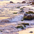 Stony seashore in the evening at sunset surf — Stock Photo