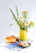 Still life with flowers and red currant bun — Стоковое фото