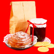 Paper bag with pastry bun and jam on a red background — 图库照片