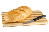 Loaf with sesame seeds on the board and knife — Stock Photo