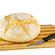 Loaf of bread on a wooden board and knife — Stock Photo