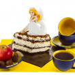 Still Life sweets and tea with a beautiful doll on the cake — Stock Photo