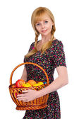 Blonde girl with a basket of ripe apples — Stock Photo