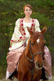 Beautiful girl in antique dress on horseback — Stock Photo