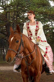 Beautiful girl in antique dress on horseback — Stockfoto