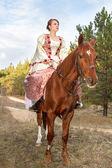 Beautiful girl in antique dress on horseback — Stock Photo