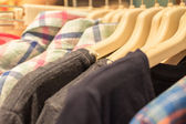 Shirts and jackets hanging on hangers in shop  — Stock Photo