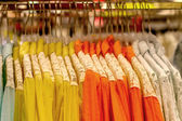 Lace shirts hanging on hangers in shop  — Stock Photo