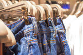 Jeans hanging on a hanger in the store  — Stock Photo
