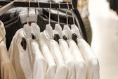 White jackets hanging on a hanger in the store — Stock Photo
