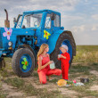 Mother feeding her son tractor in a field near the tractor — Photo #51269573