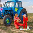 Mother feeding her son tractor in a field near the tractor — Photo #51269579