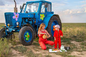 Mother feeding her son tractor in a field near the tractor  — Stock Photo