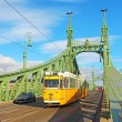 Orange tram on the Liberty bridge in Budapest, Hungary — Stock Photo