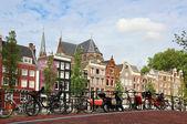 Amsterdam cityscape with bikes on the bridge — Stock Photo