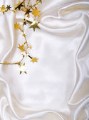 Golden stars and spangles on white silk — Stock Photo