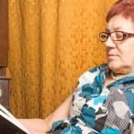 Elderly woman reading a book. — Stock Photo #20159407