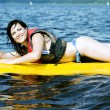 Smiling girl lies on surfing — Stock Photo #12135022
