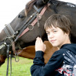 Young boy pets a horse — Stock Photo