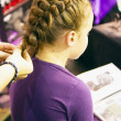 Cute little lady is plait a fashionable braid — Stock Photo