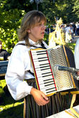 Woman in the national Latvian suit with with an accordion — Stockfoto