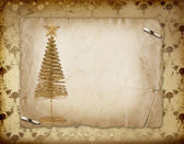 Christmas greeting card with gold metal firtree on the paper flo — Stock Photo