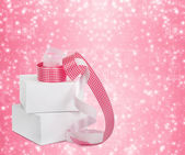 White boxes with gifts with pink ribbons on the beautiful abstra — Stock Photo