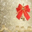 Red Christmas bow with golden bells on an abstract background — Stock Photo #29885431