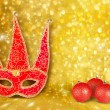 Carnival mask and a red Christmas ball on a golden abstract back — Stock Photo #31220807