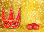 Carnival mask and a red Christmas ball on a golden abstract back — Stock Photo