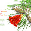 Stock Photo: Pine branch with cones and red Christmas bell on a snowy backgro