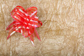 Beautiful red bow for gift decoration on abstract gold backgroun — Stock Photo