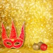 Carnival mask and a red Christmas ball on a golden abstract back — Stock Photo #32362899