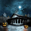 Stock Photo: Halloween pumpkins in the yard of an old house at night in the b