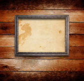 Old gilded wooden frame on grange wall — Stok fotoğraf