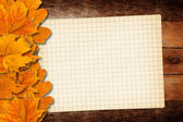 Old grunge paper with autumn leaves on the wooden background — Stock Photo